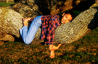 Young girl playing on the limb of a large tree.
