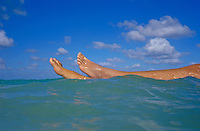 Womans legs floating in open ocean