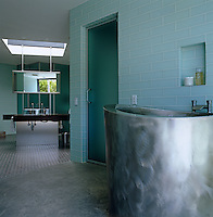 Glass tiles clad the walls of this bathroom with an oval zinc plunge tub outside the steam room
