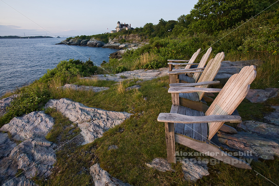 USA, Newport, RI - View north up the east passage of Narragansett Bay of Castle Hill Inn and Resort's adirondack chairs gathered on the rocky cliffs near the Castle Hill Lighthouse.