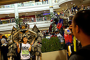 A woman poses for a photo with a giant robot at a toy-show in a mall in Manila in Philippines. Photo: Sanjit Das