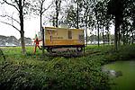 GOUDA - Vanuit een rupsvoertuig op wielen duwen medewererks van Fugro een voor een stalen buizen met meetapparatuur de grond in om metingen aan de bodem te verrichten. Terwijl de een de buizen na het steeds opnieuw de bodem in zakken, aan elkaar schroeft, houdt de ander de metingen op het scherm van zijn computer in de gaten. COPYRIGHT TON BORSBOOM