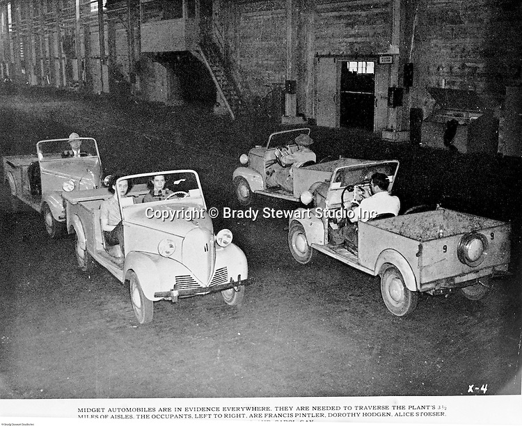 Spokane Washington and McCook Illinois: View of Swindell-Dressler brochure highlighting the Electric Furnaces designed, constructed and installed in two Alcoa plants during World War II. The caption reads:  Midget automobiles are in evidence everywhere.  They are needed to traverse the plant's 3 ½ miles of a aisles.  The occupants in the two cars facing us are, left to right, Francis Pintler, Dorothy Hodgon and Alice Stoeser.