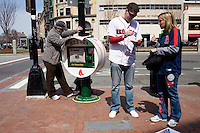 Fans wearing Red Sox apparel stand near a Red Sox-themed newspaper vending machine on the day of the 2011 Red Sox season opener in Boston, Massachusetts, USA.