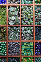 Trays of organized beads in the hues of green color found in a shop in France.