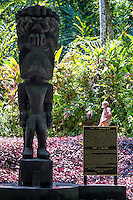 "A man stands behind the sign for the carved wooden tiki of Hawaiian god ""KU"" at the Hawai'i Tropical Botanical Garden in Onomea (near Hilo), Big Island of Hawai'i."