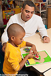 Education preschool male teacher observing as boy works on wooden puzzle encouraging him