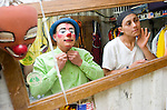 Clowns put on their makeup in a truck container before their first show of the day at a traveling tent circus.