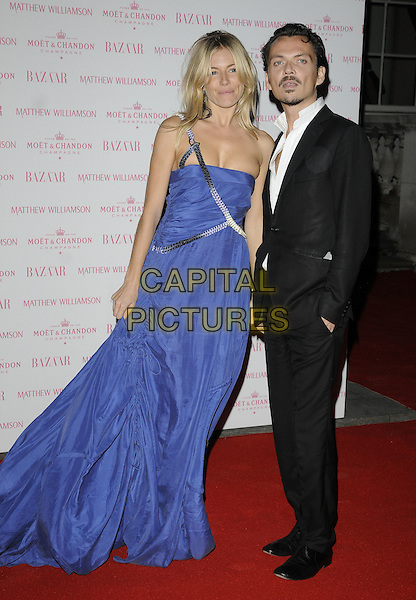 SIENNA MILLER & MATTHEW WILLIAMSON .Attending the Colin MacDowell book launch party, Somerset House, London, England, UK, October 13th 2010..full length designer muse holding hands blue cobalt long maxi dress gown suit black white shirt silver one strap shoulder .CAP/CAN.©Can Nguyen/Capital Pictures.