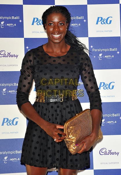 Christine Ohuruogu.The Paralympic Ball in aid of the British Paralympic Association & the Agitos Foundation, Grosvenor House Hotel, Park Lane, London, England..September 5th, 2012.half length black dress polka dot belt gold clutch bag.CAP/CJ.©Chris Joseph/Capital Pictures.