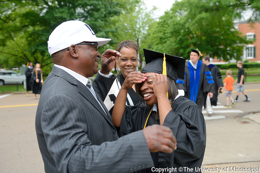 In this photo provided by The University of Mississippi, Jamila Williams of Coldwater, MS. gets some help with her mortar board from her parents just before commencement ceremonies today, Saturday, May 11, 2013.  (AP PHOTO/The University of MIssissippi/Kevin Bain)