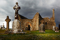 Low angle view of Clonmacnoise Cathedral, 10th century, and Cross of the Scriptures (replica), 10th century, on the left, Clonmacnoise, County Offaly, Ireland, in the evening against a cloudy sky. Clonmacnoise was founded by St Ciaran, with the help of Diarmait Ui Cerbaill, Ireland's first Christian King. The site presents the largest collection of Early Christian graveslabs in Western Europe. Picture by Manuel Cohen