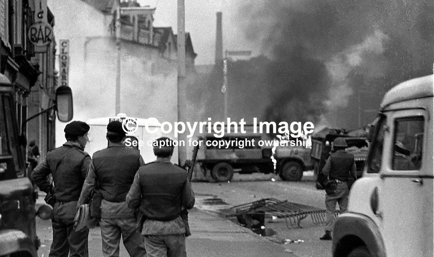 Burning barricade during the Lower Falls curfew. Soldiers look on. The British Army imposed during July 3 & 4, 1970, a 34 hour curfew (except for a two hour break to allow shopping) in approximately 50 streets in the Lower Falls district of Belfast, N Ireland, UK. A military helicopter hover overhead warning people they would be arrested if they remained on the streets. An army search during the curfew uncovered 100 firearms, 100 home-made bombs, 250 lbs of explosives, 21000 rounds of ammunition and 8 two-way radios. This curfew is often seen as a turning point in souring relations between the Roman Catholic working class and the British Army. Thereafter the army was no longer seen as the protector of the Catholic community. 197007030251R. ..Copyright Image from Victor Patterson, 54 Dorchester Park, Belfast, UK, BT9 6RJ..Tel: +44 28 9066 1296.Mob: +44 7802 353836.Voicemail +44 20 8816 7153.Skype: victorpattersonbelfast.Email: victorpatterson@mac.com.Email: victorpatterson@ireland.com (back-up)..IMPORTANT: If you wish to use this image or any other of my images please go to www.victorpatterson.com and click on the Terms & Conditions. Then contact me by email or phone with the reference number(s) of the image(s) concerned.