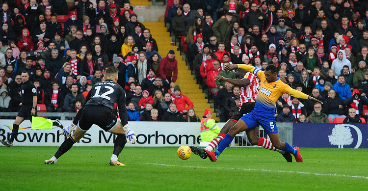 Lincoln City's John Akinde, under pressure from Mansfield Town's Krystian Pearce, sees his shot saved by Mansfield Town's Robert Olejnik<br /> <br /> Photographer Chris Vaughan/CameraSport<br /> <br /> The EFL Sky Bet League Two - Lincoln City v Mansfield Town - Saturday 24th November 2018 - Sincil Bank - Lincoln<br /> <br /> World Copyright © 2018 CameraSport. All rights reserved. 43 Linden Ave. Countesthorpe. Leicester. England. LE8 5PG - Tel: +44 (0) 116 277 4147 - admin@camerasport.com - www.camerasport.com
