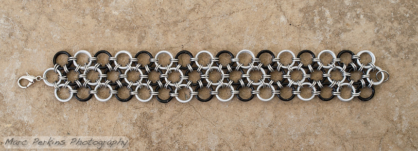 "A chainmail bracelet made by Michelle in a Japanese 12-in-2 pattern from 18 gauge 1/4"" black and white anodized aluminum rings with 20 gauge 1/8"" bright aluminum rings as connectors.  Taken on a concrete floor for a rugged background."