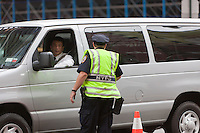 A NYPD police officer screens vehicle as they pass through a security checkpoint on 44th Street between 7th and 8th Avenues.