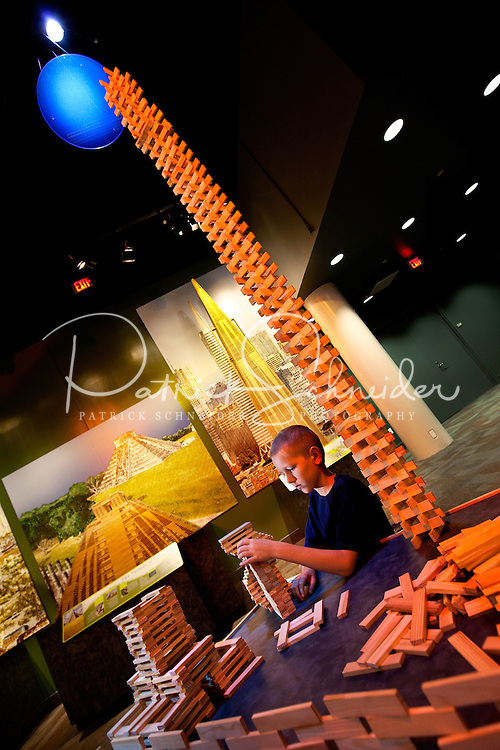 "Visitors to Charlotte's Discovery Place museum check out Project Build, an interactive hands-on learning lab created to inspire inquiry-based  learning. Here, a child tries out a ""bed of nails."" Discovery Place, Charlotte NC's interactive children's museum, unveiled its interactive exhibits and hands-on activities in June 2010. Renovations of the popular family museum were made possible by the City of Charlotte, the Arts and Science Council and private donations. Discovery Place museum has age-appropriate exhibits for kids of all ages."