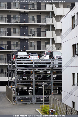 Cars parked in a multi-level vertical three-storey automated parking lot with a lift by an apartment building in Kyoto, Japan 2017
