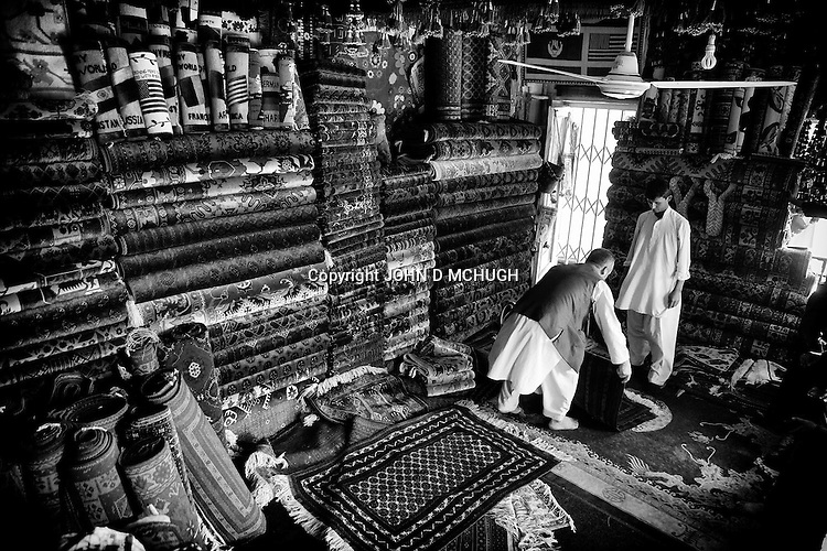 Carpet sellers are seen examining their wares in mazar-e Sharif, 25 September 2013. (John D McHugh)