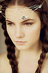 Close portrait of young woman with braids and pearl headpiece