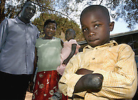 Najib Ssemambo, 4, right lost his hand in what his father Moses Wassawa says was negligence. He is suing a Kampala, Uganda hospital in the case.  Najib's mother Safina Nakitto holds the boy's sister Zahara Nagujja, 3.  Jan. 21, 2004. (Rick D'Elia)