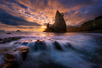 A gem of the Olympic Peninsula, Rialto beach has many such sea stacks rising from its depths.  One particularly photogenic spire collapsed within the last year.  The remnants from its collapse are now being interred by the sea. This particular evening, an incoming tide produced beautiful cascades across its fractured remains.<br />