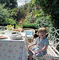A boy sits on a painted metal garden bench in fornt of a table set for lunch
