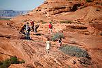 Tourists walk among the red rocks near Horseshoe Bend.