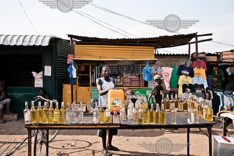 A man selling cooking oil from a stall in Nakambala Market.