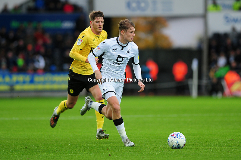 Jason McCarthy of Millwall vies for possession with George Byers of Swansea City during the Sky Bet Championship match between Swansea City and Millwall at the Liberty Stadium in Swansea, Wales, UK. Saturday 23rd November 2019