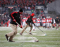 Ohio State Buckeyes ground crews clear the snow from the yard lines after the third quarter of the Ohio State Buckeyes and Indiana Hoosiers college football game at Ohio Stadium in Columbus, Ohio on November 23, 2013.  (Dispatch photo by Kyle Robertson)