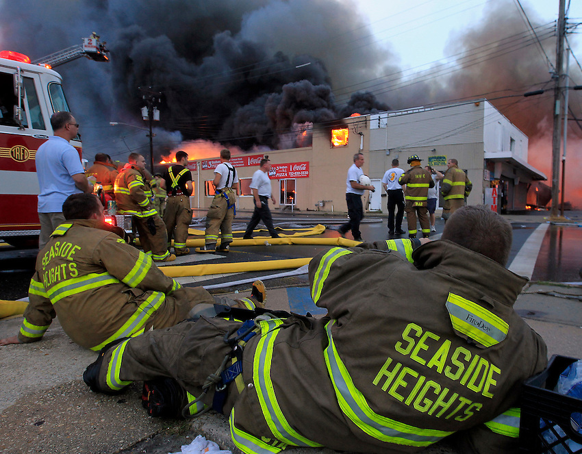 SEASIDE HEIGHTS, NJ (Sept. 12, 2013) - Three hours into the battle, Seaside Heights firefighters take a break as wind-swept flames continue to consume the boardwalk.