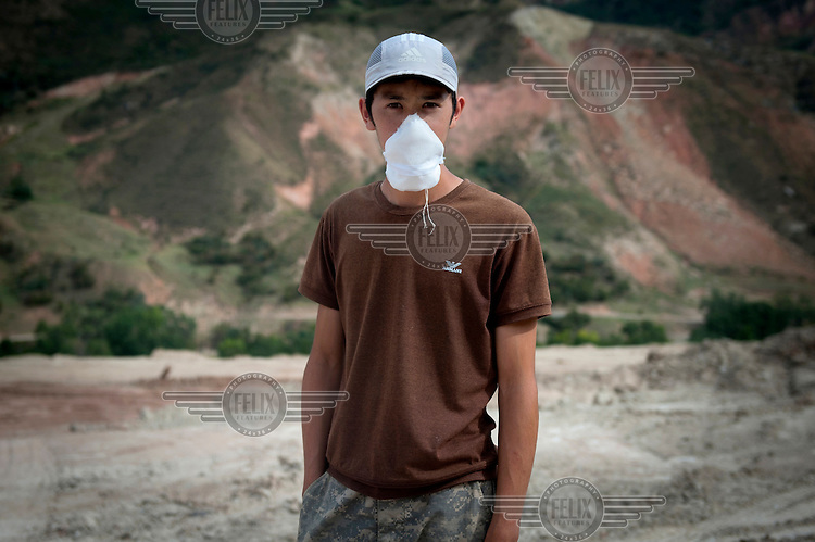 Nurdin Stamkulov, 21, stands at the entrance of Dump No.6 where he works. Workers make about 20,000 Somoni (GBP 2,650) in 2 weeks. Due to the pollution they ingest while working, staff work two weeks on and two weeks off....