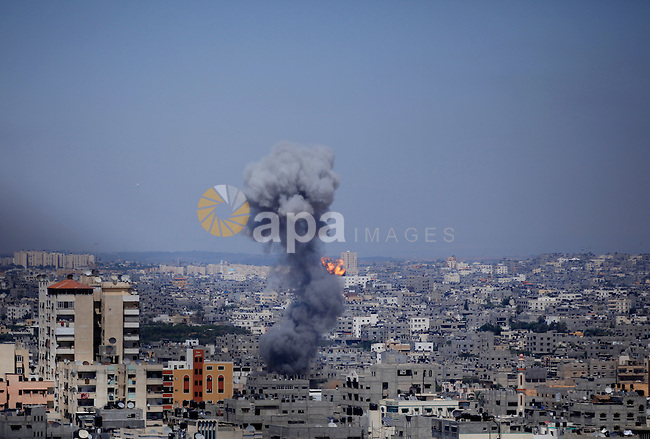 Smoke billows from buildings following an Israeli air strike in Gaza City on July 9, 2014. Israeli air strikes shook Gaza every few minutes on Wednesday, and militants kept up rocket fire at Israel's heartland in intensifying warfare that Palestinian officials said has killed at least 53 people in the Hamas-dominated enclave. Photo by Mohammed Othman