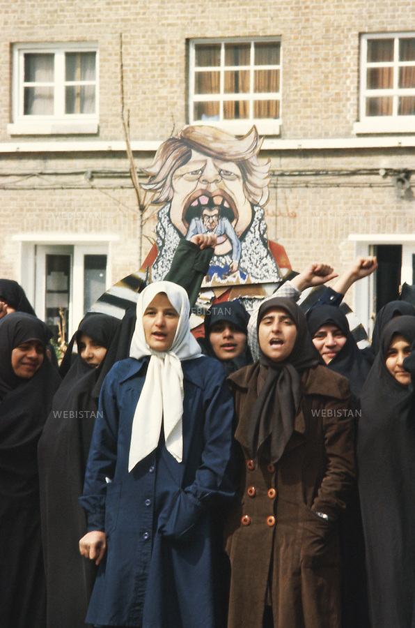 TEHRAN, IRAN - NOVEMBER 1979: While holding a caricature of Mohammad Reza Pahlavi, the last shah of Iran inside the mouth of Jimmy Carter, the U.S. president at that time, a group of women shout slogans against the U.S. goverment at the demonstration in front of the U.S. embassy during the hostage crisis which was a diplomatic crisis between Iran and the United States where 52 U.S. diplomats were held hostage for 444 days from November 4, 1979 to January 20, 1981, after a group of Islamist students took over the American embassy in support of the Iranian revolution.(Photo by Reza/Webistan).<br /> T&eacute;h&eacute;ran, Iran - Novembre 1979. Portant une caricature de Mohammad Reza Pahlavi le dernier shah d'Iran, dans la bouche de Jimmy Carter, le pr&eacute;sident des Etats Unis, un groupe de femmes crie des slogans contre le gouvernement am&eacute;ricain  pendant une manifestation de soutien aux preneurs des otages am&eacute;ricains et &agrave; la r&eacute;volution iranienne. La crise des otages &agrave; T&eacute;h&eacute;ran fut une crise diplomatique entre l'Iran et les Etats Unies durant laquelle 52 diplomates am&eacute;ricains furent pris en otage par un groupe d'&eacute;tudiants islamistes apr&egrave;s qu'ils se soient empar&eacute;s de  l'ambassade am&eacute;ricaine dans le cadre de leur soutien &agrave; la r&eacute;volution islamique. Les otages rest&egrave;rent  prisonniers pendant 444 jours du 4 novembre 1979 au 20 janvier 1981 (Photo de Reza/Webistan)