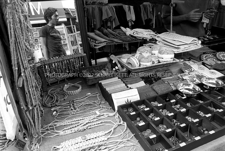 """8/10/2002--Shimokitazawa, Tokyo, Japan..A street vendor sells beads, bracelets and other paraphenalia for Shimo's hip...Wedged between Tokyo's Shinjuku and Shibuya wards, Shimokitazawa's maze of narrow streets form the ramparts of all that is non-conformist in get-along, go-along Japan. In """"Shimokita,"""" old village shops trade happily beside newer, eccentric clothing stores, funky restaurants, matchbox playhouses and live-music clubs. The unpretentious ambience is a magnet for students and other young visitors for whom Tokyo's usual street fashion scene has become more fascist than fun and mainstream entertainment is, well, too mainstream. Musicians, designers, aspiring actors and other would-be iconoclasts have settled the area, as have young professionals opting for a less-structured lifestyle. ...All photographs ©2003 Stuart Isett.All rights reserved.This image may not be reproduced without expressed written permission from Stuart Isett."""