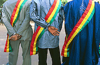 Mali. Province of Segou. Niono. October 16 2003. Worlwide food day. The people's representatives of the area wear on their clothes the tricolour cockade (the malian flag: green, yellow and red ) while waiting for the arrival of the malian president Amadou Toumani Toure (ATT). Three men are seen from behind;  two are dressed with western clothes and the third wears the traditional malian suit, the Boubou. © 2003 Didier Ruef