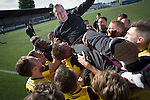 Visiting players celebrating promotion by throwing manager Gary Jardine in the air after East Stirlingshire hosted Edinburgh City in the second leg of the Scottish League pyramid play-off at Ochilview Park, Stenhousemuir. The play-offs were introduced in 2015 with the winners of the Highland and Lowland Leagues playing-off for the chance to play the club which finished bottom of Scottish League 2. Edinburgh City won the match 1-0 giving them a 2-1 aggregate victory making them the first club in Scottish League history to be promoted into the league.