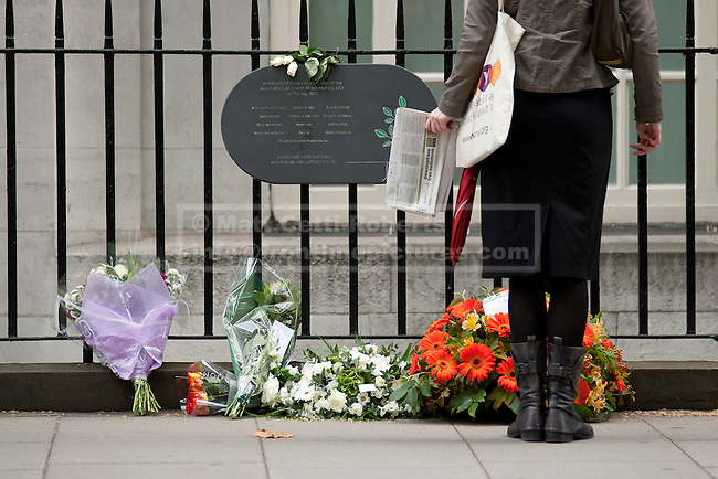 LONDON, UK  07/07/11. A passer by looks at flowers laid at the Tavistock Square Bomb Memorial in London. The memorial remembers the 14 people who died on July the 7th 2005 at 08:50 when suicide bomber Hasib Hussain detonated his bomb on the Number 30 bus passing by the spot. The attack was one of 4 that were set off that day causing 56 deaths and hundreds of injuries. Please see special instructions for usage rates. Photo credit should read Matt Cetti-Roberts