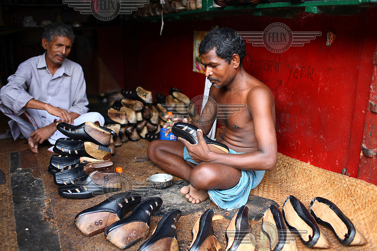 A cobbler makes shoes by hand at his small factory in Kolkata.