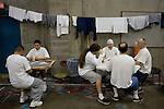 Inmates play cards next their drying laundry in crowded gymnasiums coverted into dormitories at the California State Prison Ð Sacramento in Folsom, California, Thursday, Dec. 7, 2006. The California prison system is so crowded that 16,000 inmates are assigned cots in hallways and gyms Ð leading Gov. Arnold Schwarzenegger to declare a state of emergency for the system.
