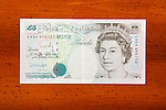 Five pound British currency note on table showing Queen Elizabeth II