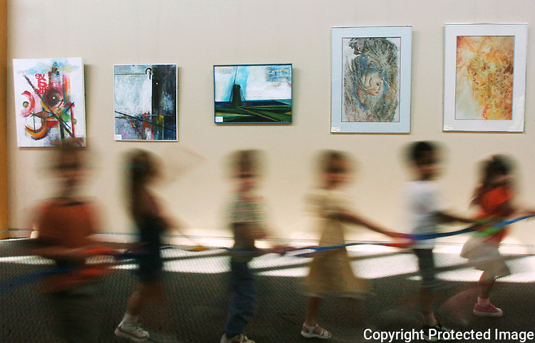 Preschool children parade through the main hallway of the San Marcos Community Center where artworks of several artists are on display.  photo for North County Times