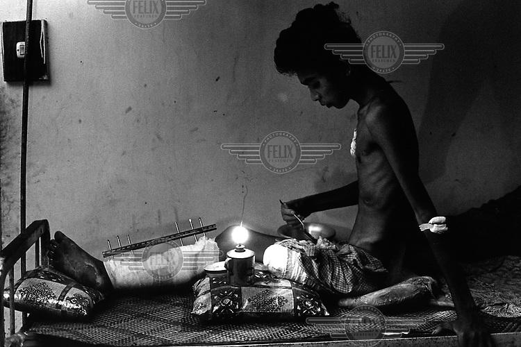 Foto Jan Banning..Cambodja. Jongeman, slachtoffer van een landmijn, tijdens het eten bij het licht van een olielamp in het ziekenhuis van Siem Reap. Zijn overgebleven been moet ook geamputeerd, aldus de chirurg van MSF (Artsen Zonder Grenzen), maar hij weigert. De volgende dag zal hij vertrekken naar een traditionele genezer - en, aldus de chirug, kort daarop waarschijnlijk sterven...Cambodia. Young man, land mine victim, eating an oil lamp dinner in the hospital of Siem Reap. His remaining leg should also be amputated, according to the surgeon of MSF (Doctors without Borders). The patient refuses, and the next day he will leave for a traditional bare-foot doctor. According to the surgeon, that will mean an almost certain death.