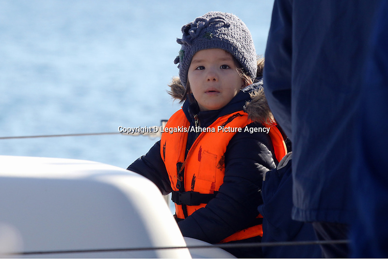 Pictured: A young boy wearing a life vest looks bemused as the vessel carrying him and other illegal immigrants are about to disembark to Ierapetra Thursday 27 November 2014<br />