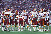 Washington Redskins offense huddles on the field at the Hubert H. Humphrey Metrodome in Minneapolis, Minnesota during a break in the action during Super Bowl XXVI.  Pictured, from left to right, tackle Jim Lachey (79), tight end Terry Orr (89), guard Raleigh McKenzie (63), center Jeff Bostic (53), running back Earnest Byner (21), guard Mark Schlereth (69), guard Joe Jacoby (66), quarterback Mark Rypien (11), wide receiver Gary Clark (84), tight end Don Warren (85), and wide receiver Art Monk (81).<br /> Credit: Arnie Sachs / CNP