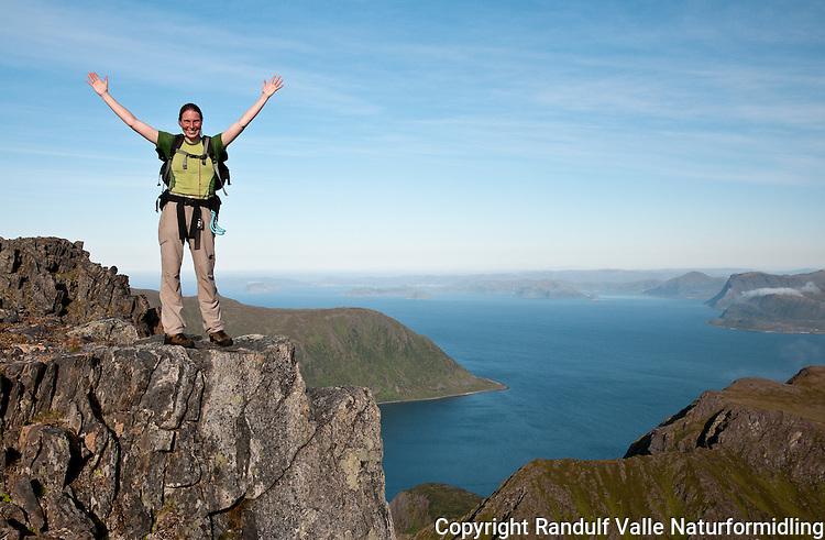 Dame på toppen av Komagaksla, det høyeste fjellet på Sørøya. Sørøysundet og Seiland i bakgrunnen. ----- Woman on top of Komagaksla, the highest point on Sørøya.
