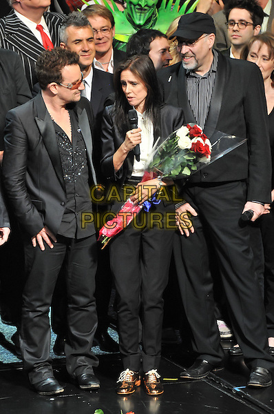 "BONO (Paul Hewson) of U2 & Julie Taymor.The Broadway Opening of ""Spider-Man Turn Off The Dark"" - Curtain Call, New York City, NY, USA..June 14th, 2011.gv general view stage black suit clapping full length bouquet flowers profile.CAP/ADM/CS.©Christopher Smith/AdMedia/Capital Pictures."
