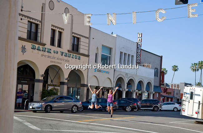 Two young woman posing for a photo jump in the air beneath the Venice Sign in Venice Beach, CA