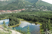 "Multiple hotels are clustered near the entrance to Denali National Park in an area Alaskans call ""Glitter Gulch."" Horseshoe Lake is in the foreground. The Alaska Railroad's Denali Star train runs between Anchorage and Fairbanks, with Denali one of the stops along the way."